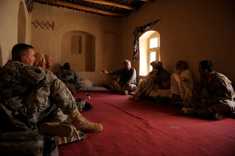 """Dr. Jim Helton, U.S. Agency for International Development field program officer, working with Provincial Reconstruction Team Zabul, speaks with the Khalqdad Khan village elder during a meeting in the elder's home May 24, 2010, in Khaleqdad Khan, Afghanistan. ?As PRT Soldiers and Airmen funnel in and out they add to the reconstructive development and sustainability we build as a team,"""" Dr. Helton said. """"When we share the same vision and are well-integrated we are able to serve the people of Zabul as on single-minded unit focused on serving the Afghan people here.? (U.S. Air Force photo/Staff Sgt. Manuel J. Martinez/released)"""