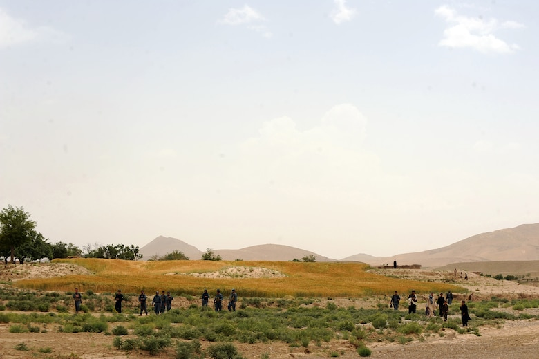 Afghan National Police and Afghan civilians wait for Airmen and Soldiers assigned to Provincial Reconstruction Team Zabul,  to arrive at a village for a Shura meeting in the Omarkhel village May 22, 2010,in Zabul Province, Afghanistan. (U.S. Air Force photo/Staff Sgt. Manuel J. Martinez/released)