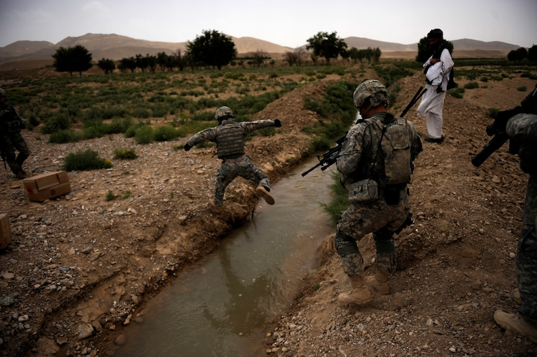 """?Craft,"""" an interpreter working with Provincial Reconstruction Team Zabul, crosses a creek on the way to Omarkhel village for a Shura May 22, 2010, in Zabul Province, Afghanistan. (U.S. Air Force photo/Staff Sgt. Manuel J. Martinez/released)"""