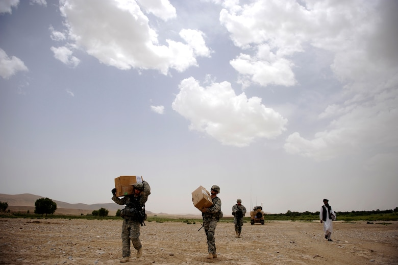 Airmen and Soldiers assigned to Provincial Reconstruction Team Zabul, carry boxes of coloring books that will be handed out to village children during a Shura mission in the Omarkhel village May 22, 2010, in Zabul Province, Afghanistan. Provincial Reconstruction Team Zabul members are working side-by-side with provincial government officials to bring reconstruction, regional development, credible governance and security to Zabul. (U.S. Air Force photo/Staff Sgt. Manuel J. Martinez/released)