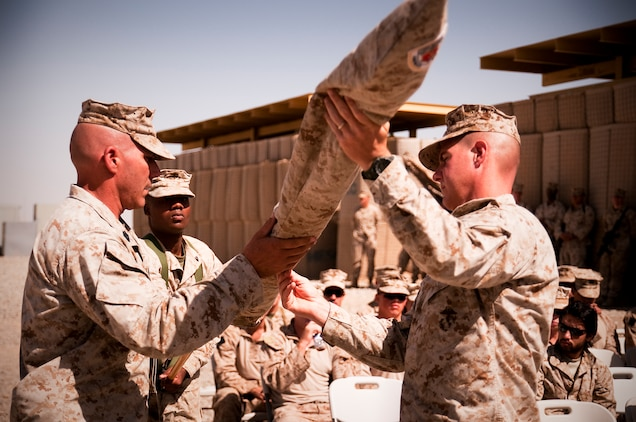 Lt. Col. Jeffrey C. Holt and Sgt. Maj. Andrew T. Cece, commanding officer and sergeant major, 3rd Battalion, 3rd Marine Regiment, unfurl the battalion colors during a transfer of authority ceremony at Forward Operating Base Geronimo where 3/3 took over 1st Battalion, 3rd Marine Regiment's are of operations, June 6.