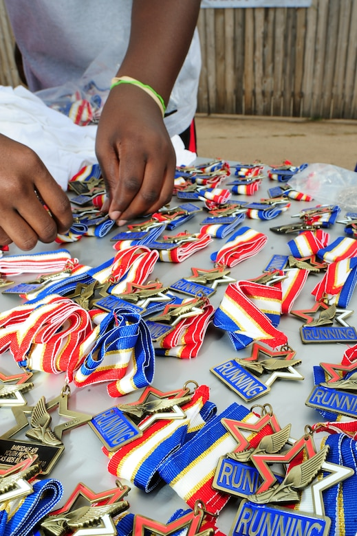 BARKSDALE AIR FORCE BASE, La. – A youth center volunteer lays 'running medals' out for America's Armed Forces Kids Run participants outside the fitness center June 4. Participants, ranging from ages 5-13, ran a half-mile, one mile or two miles depending on their age category. (U.S. Air Force photo by Senior Airman Joanna M. Kresge)
