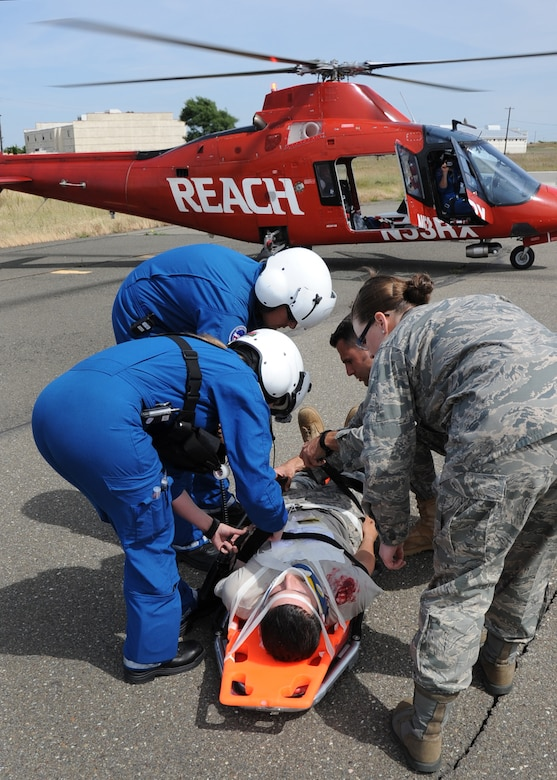 During an emergency response exercise at Travis Air Force Base on 12 May 2010 a local civilian air ambulance and military medical personal work together to transport a simulated patient.  (U.S. Air Force photo by Civ/Jay Trottier)
