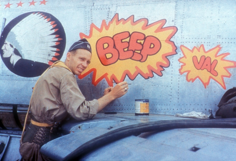 "Fighter aircraft often carried decorative ""nose art"" in Korea. Pictured here is Capt. Karl Dittmer Jr., an F-86 pilot with three MiG kills, at work. Dittmer painted nose art on many of the 335th Fighter Interceptor Squadron's Sabres at Kimpo. (U.S. Air Force photo)"