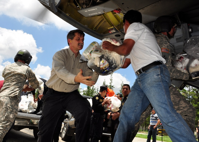 U.S. Ambassador to Guatemala, Stephen McFarland, helps offload food and water from a Joint Task Force-Bravo CH-47 Chinook June 5 in the community of Santa Cruz del Quiche, Guatemala. Joint Task Force-Bravo's helicopters have transported approximately 94,000 pounds of relief supplies since June 2 to Guatemalan communities in need. (U.S. Air Force photo by Staff Sgt. Bryan Franks)