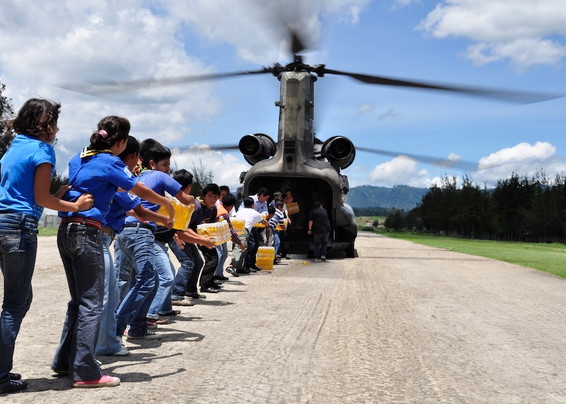 Young and old alike begin offloading food and water from a Joint Task Force-Bravo CH-47 Chinook June 5 in the community of Santa Cruz del Quiche, Guatemala. Joint Task Force-Bravo's helicopters have transported approximately 94,000 pounds of relief supplies to Guatemalan communities since June 2, in support of the Guatemalan government's disaster relief efforts following the Pacaya Volcano eruption and Tropical Storm Agatha. (U.S. Air Force photo by Staff Sgt. Bryan Franks)