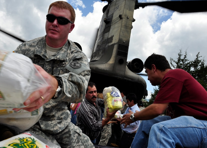U.S. military members and people from Santa Cruz del Quiche, Guatemala, offload disaster relief supplies from a Joint Task Force-Bravo CH-47 Chinook June 5. Joint Task Force-Bravo's helicopters have transported approximately 94,000 pounds of relief supplies since June 2 to Guatemalan communities in need. (U.S. Air Force photo by Staff Sgt. Bryan Franks)