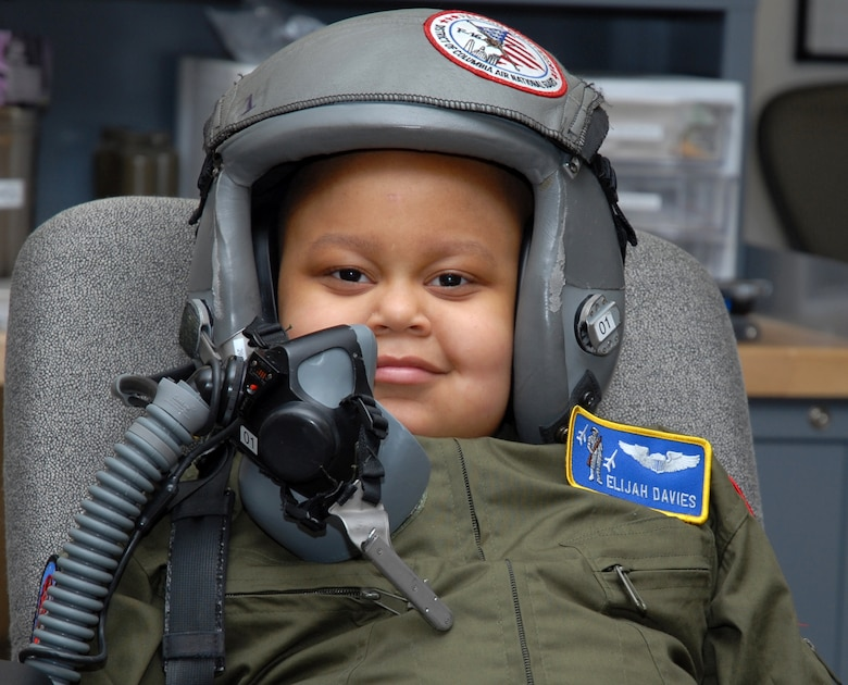 The Pilot for a Day, Elijah Woods, who is recovering from two major surgeries to remove a brain tumor, receives a demonstration of flight gear prior to getting into an F-16 flight simulator with the 121 FS at Andrews Air Force Base, 22 April 2010.
