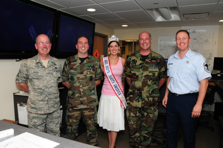 Newly crowned Mrs. North Dakota America, Tech. Sgt. Tera Miller, of the 119th Operations Support Squadron, visits her work area June 7, at the North Dakota Air National Guard, Fargo, N.D.  She is surrounded by her coworkers from left to right, Senior Master Sgt. Kevin Nelson, Tech. Sgt. Christopher Schatzke, Master Sgt. Brian Rook, and Senior Master Sgt. Scott Flickinger.  Miller was selected 2010 Mrs. North Dakota America at the Grand Masonic Lodge, June 6, in Fargo.  One of Millers competitors for the crown was fellow Guard member SGT. Jill Johnson, with the North Dakota Army National Guard.  Miller will advance to the national Mrs. America pageant in Tuscan, Ariz., in September. Miller, along with her twin sister Tech. Sgt. Lisa Narum joined the North Dakota Air National Guard in 2001. (DoD photo by Senior Master Sgt. David H. Lipp)