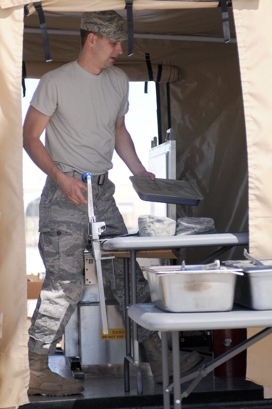Staff Sgt. Jake Sulwer, prepares unitized group rations on the flightline at Tucson International Airport, June 5. Sulwer, and other members of the 162nd Services Flight, practiced using a Single Pallet Expeditionary Kitchen during a drill weekend here. (Air Force photo by Airman First Class Krystal Tomlin)