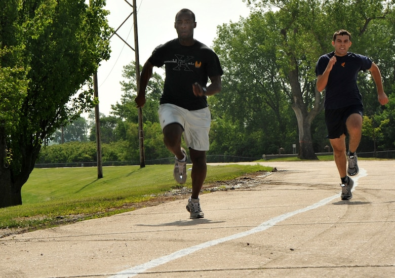 OFFUTT AIR FORCE BASE, Neb. - 1st Lt. David Omolayo from the 338th Combat Training Squadron, pulls ahead of James Butler, a Reserve Officer Training Corps cadet from the University of Nebraska at Omaha, in the 110 yard dash event here during the 55th Wing's annual Sports Day. Sports Day offered many events including  ultimate Frisbee, volleyball, a 5K race and much more. The event is designed to promote good health and increase unit morale. U.S. Air Force Photo by Jeff W. Gates.