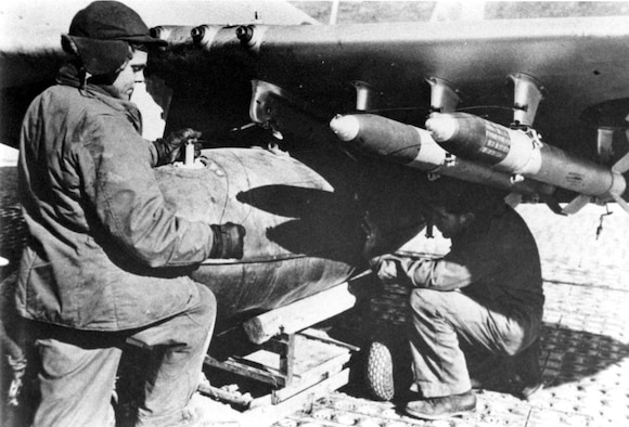 Armorers load a napalm bomb onto the wing of an F-51D. Napalm is a mixture of gasoline and a thickening agent which gives it the consistency of jelly. (U.S. Air Force photo)