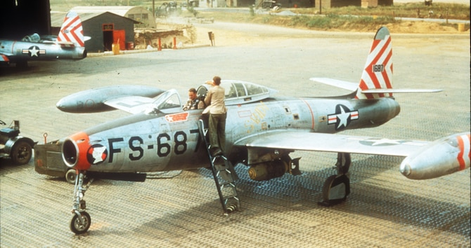 F-84 crew chief cleans the canopy as the pilot straps in before a mission. (U.S. Air Force photo)