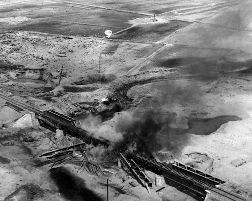 Rail bridge at Sunan, North Korea, under attack. In the upper middle part of the photo is a parachute bomb. The parachute slowed the rate of descent for low altitude bombing -- otherwise, the bomb would detonate directly below the attacking aircraft. U(U.S. Air Force photo)