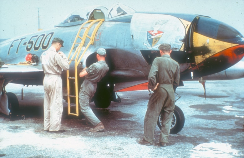An F-80 pilot removes his flight gear as the ground crew checks the aircraft after a mission. (U.S. Air Force photo)