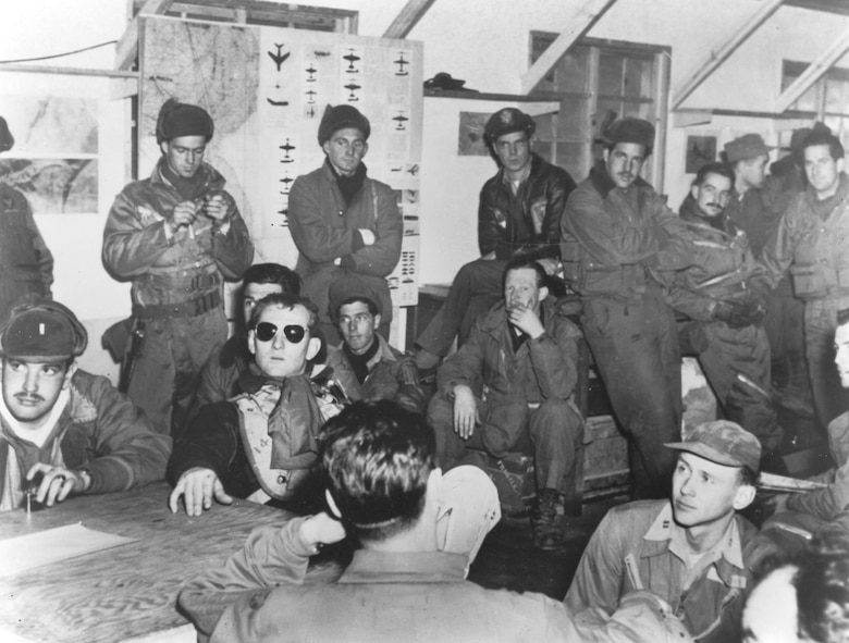 Tired USAF and Royal Australian Air Force Mustang pilots are debriefed after an attack on communist forces southeast of Seoul in February 1951. (U.S. Air Force photo)