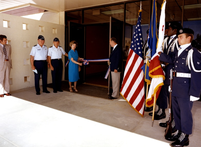 Col. Jackie L. Ridley 's widow, Mrs. Nell Ridley Loe, and retired Brig. Gen. Chuck Yeager (right of the door) cut the ceremonial ribbon to the Ridley Mission Control Center, June 12, 1980.  General Yeager, who flew with Colonel Ridley and was a close friend, said supersonic flight may not have been achieved without Colonel Ridley's analysis and intellect. (Official Air Force photo)