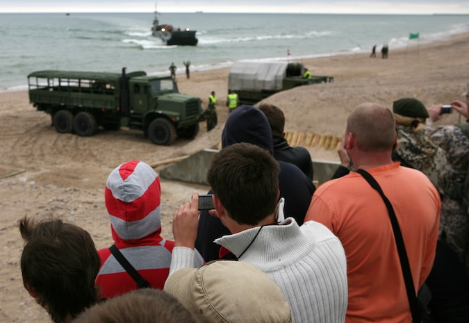 Local Latvian citizens and members of the National Armed Forces of Latvia observe a beach landing where Marines and Sailors participating in exercise BALTIC OPERATIONS 2010 conduct a maritime preposition force (MPF) offload of vehicles and equipment. The MPF offload portion is one of largest portions of exercise BALTOPS, a multinational maritime exercise designed to increase interoperability between the 12 participating nations and increase maritime safety and security.