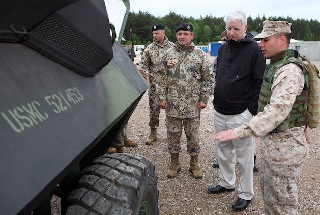 Lance Cpl. Noah Peczeli (right), a light armored reconnaissance vehicle (LAV) mechanic with 4th Landing Support Battalion, explains the mechanical capabilities of the engine in the LAV to the Latvian Minister of Defense Imants Liegis (center), and Maj. Gen. Juris Maklakovs (left), the Commander of National Armed Forces of Latvia. The Minister of Defense and Chief of Defense visited several sights in the Ventspils area where U.S. and Latvian forces are working together to conduct a maritime preposition offload exercise.