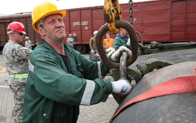 A civilian railway engineer attaches a hoist cable to an M1A1 Main Battle Tank during the rail-way movement portion of the maritime preposition force (MPF) offload portion of exercise BALTIC OPERATIONS 2010. The MPF offload portion is one of largest portions of exercise BALTOPS, a multinational maritime exercise designed to increase interoperability between the 12 participating nations and increase maritime safety and security.