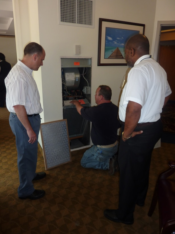 Mr. Barcomb, left, and lodging operations manager Bob Jones look on as evaluator Tom Rafferty explains ways to reduce the base's energy consumption.  (U.S. Air Force photo by Scott Lawless)