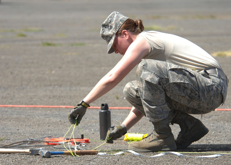 An Airman from the 146th Civil Engineering Squadron assists with measuring on a construction site on Pearl City's Naval base in Hawaii June 7, 2010. The Civil Engineering Squadron will be assisting with various construction projects over the course of two weeks including Barbers Point Coast Guard Base. (DoD photo by Airman 1st Class Nicholas Carzis, U.S. Air Force/Released)