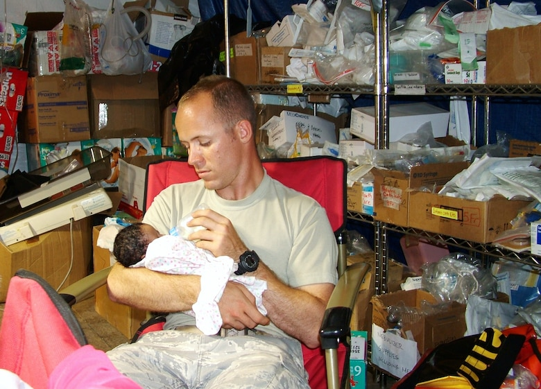 First Lt. Michael Capra, 3rd Combat Communications Support Squadron, Tinker Air Force Base, Okla., cares for a baby at the University of Miami Hospital, Port-Au-Prince airport location. Members of the 3rd Combat Communications Group were supporting relief efforts in Haiti since February and the last remaining members returned home in June. (US Air Force photo)