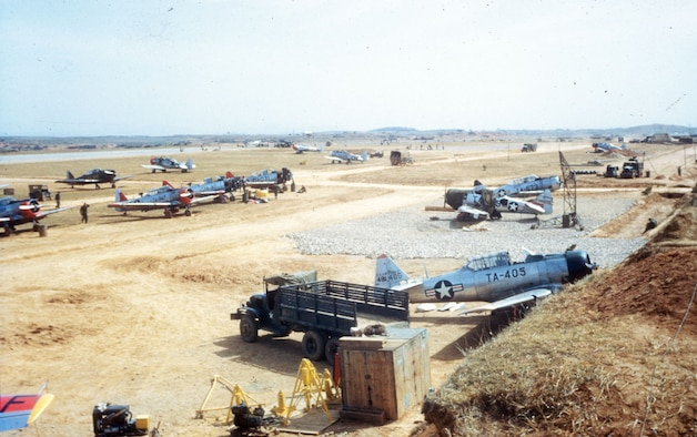 "Mosquitos at K-6 (Pyongtaek) in the spring of 1951. The maintenance ""shop"" is the open-air gravel pad on the right of the photo. The taxiways are dirt and the PSP (pierced steel planking) runway is in the background on the left. (U.S. Air Force photo)"