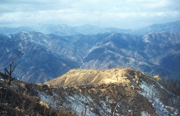 Desolate UN trench line along the mountainous 38th Parallel (also called the Main Line of Resistance or MLR). Heartbreak Ridge, a fiercely contested position, is visible in the background. (U.S. Air Force photo)