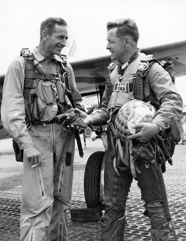 Upon completing his 100th and final mission in F-84 Thunderjets, Col. Victor Warford (left), 58th Fighter Bomber Wing (Reinforced) commander, hands over his gun to his deputy, Col. Joseph Davis Jr. (U.S. Air Force photo)