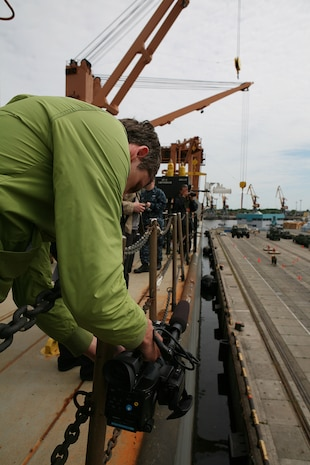 A member of the Latvian press films a demonstration of lift on/lift off operations from the side of the USNS Pfc. Eugene A. Obregon, a maritime preposition force (MPF) ship, during a demonstration designed to highlight the types of training that have taken place during exercise Baltic Operations 2010. The MPF offload operations demonstrated here make up one of the largest portions of exercise BALTOPS, a multinational maritime exercise designed to increase interoperability between the 12 participating nations and increase maritime safety and security.
