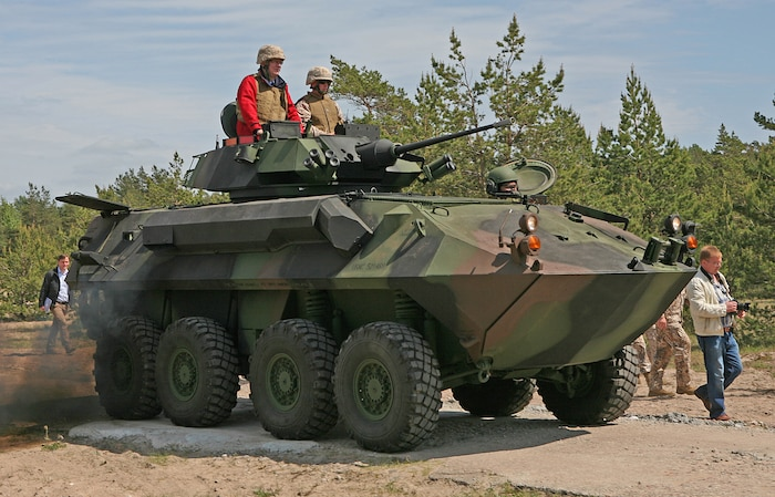 Latvian President Valdis Zatlers (in red on top of vehicle) rides a Light Armored Reconnaissance Vehicle that had moved ashore after being offloaded the USNS Pfc. Eugene A. Obregon, a maritime preposition force (MPF) ship, during a demonstration designed to highlight the types of training that have taken place during exercise Baltic Operations 2010. President Zatlers visited the Marines and Sailors of 4th Landing Support Battalion and Naval Beach Group 2, who have been working together with Latvian forces to conduct MPF offload operations and other training events here since the start of the exercise June 6.