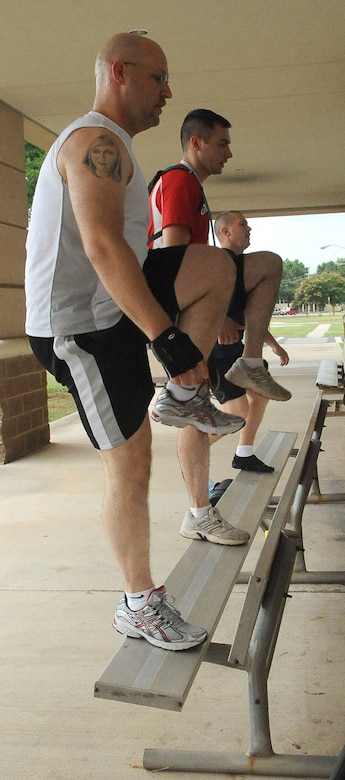 """BARKSDALE AIR FORCE BASE, La. -- Airmen perform """"step ups"""" on a bench during the Health and Wellness Center?s basic training class June 9. The class is designed to improve an individual's overall health and physical fitness and is held 5:15 p.m. Monday through Thursday in front of the base fitness center. (U.S. Air Force photo/Senior Airman Amber Ashcraft) (RELEASED)"""