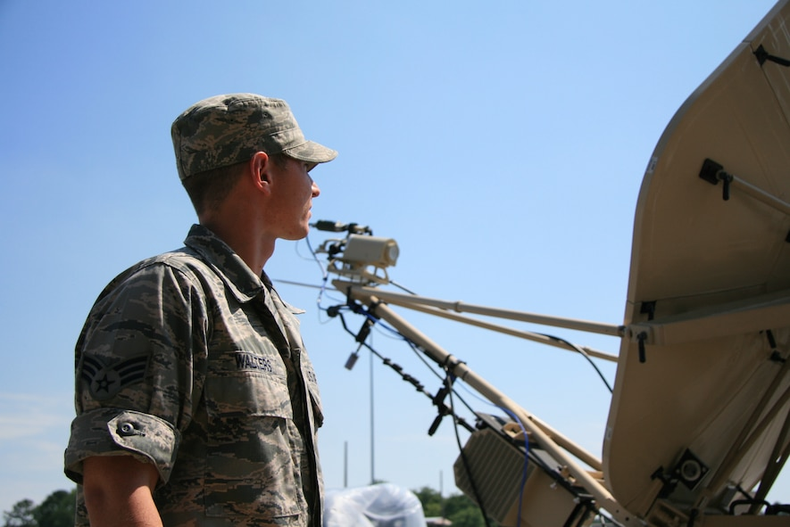 ROBINS AIR FORCE BASE, Ga. - Senior Airman Patrick Walters, a 52nd Combat Communications Squadron Radio Frequency Transmission Systems journeyman, watches as the Quad-Band Dual Hub satellite communications antenna terminal (QHSAT) adjusts itself while tracking its synchronized satellite, June 8. Airman Walters, whose career field recently merged radio and satellite specialists, is learning more about combat comm satellite operations as part of the Joint User Interface Communications Exercise, or JUICE, here, June 7-25. (U.S. Air Force photo/2nd Lt. Joel Cooke)