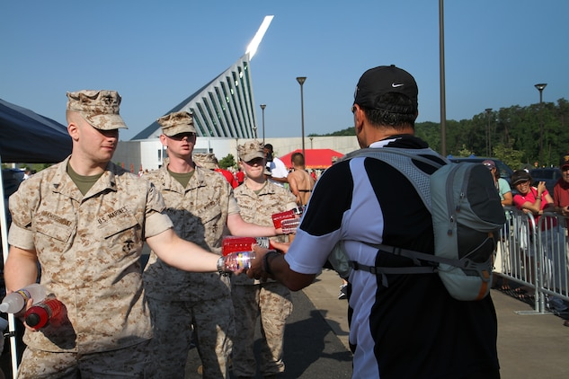 Cpl. Daniel R. Dambrowski, an administrative clerk with Headquarters & Service Battalion, Marine Corps Base Quantico, Va., hands a runner water and a sports drink along with other Marines from his unit at the finish line of the Marine Corps Marathon Crossroads 17.75K June 12, 2010. The Marine Corps offered hospitality in the form of water, sports drinks and snacks to replenish the runners after the 11 mile ordeal.