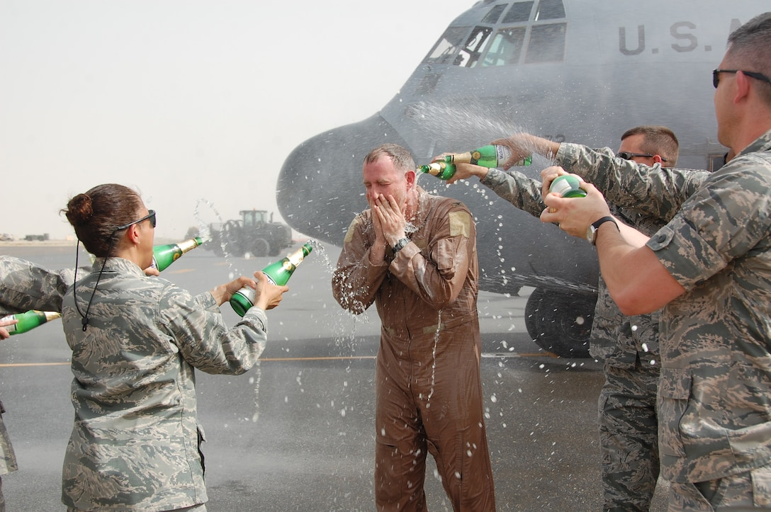 U.S. Air Force members of the 386th Air Expeditionary Wing douse Col. John R. Gordy II, 386th AEW commander, with non-alcoholic sparking champagne after he completed his last flying mission here June 12, 2010 at an undisclosed location in Southwest Asia. Colonel Gordy will relinquish command of the 386th AEW in a ceremony later this month and then head to his next assignment at the Pentagon.  Colonel Gordy is a master navigator with more than 4,700 flight hours in C-130 E/H and T-43 aircraft.  (U.S. Air Force photo/Staff Sgt. Lakisha A. Croley)