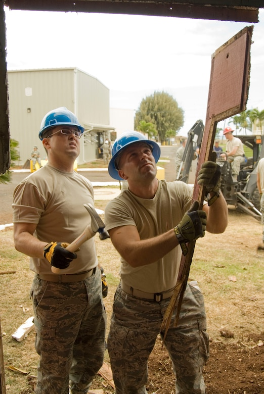 Airman 1st Class Jose Barquero and Airman 1st Class George Kozumplik tear down the remainder of what used to be a wall at the multi-purpose building at USCG Air Station Barbers Point, Hawaii, June 10, 2010. The Civil Engineering Squadron was assigned the task of remodeling the multi-purpose building used by Coast Guard personnel on site. (DoD photo by Airman 1st Class Nicholas Carzis, U.S. Air Force)