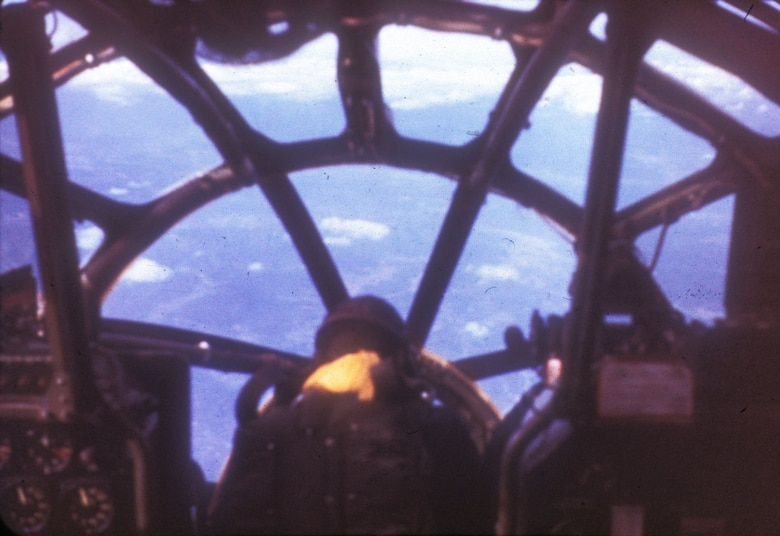 B-29 bombardier hunched over the bombsight in the nose. (U.S. Air Force photo)