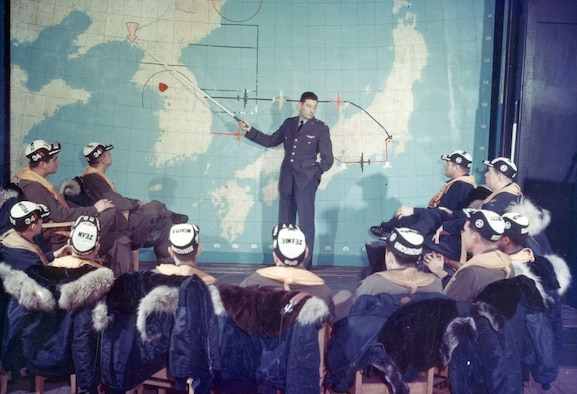 Maj. Harry Bailey points out the often-visited target of Sinuiju, North Korea. On the right of the map is a red dot that represents their starting point, Yokota Air Base near Tokyo, Japan. (U.S. Air Force photo)