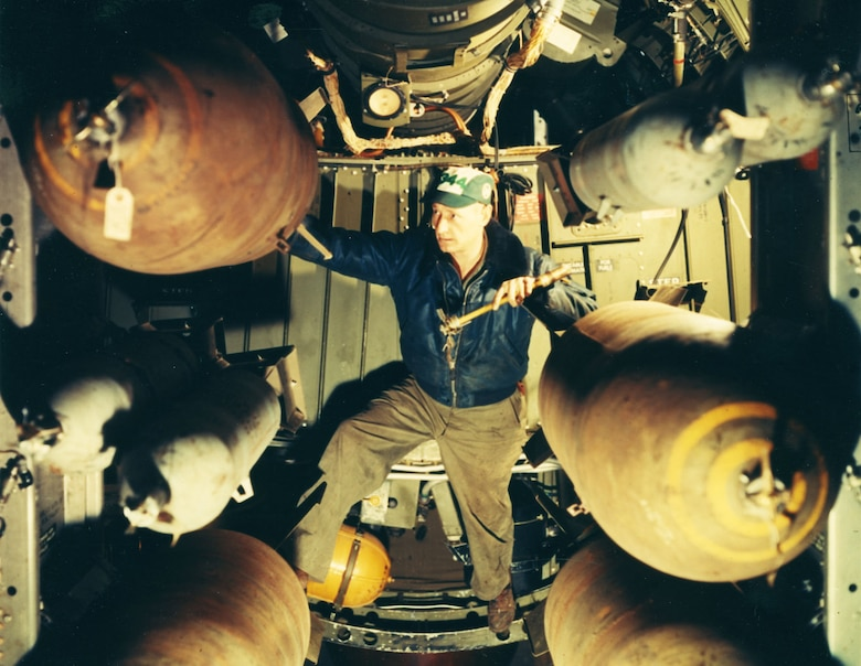 Airman 1st Class W.W. Wood of the 19th Bomb Group inserts a tail fuse into 1,000-lb. high-explosive bomb prior to a night attack. The gray photoflash bombs are dropped at the same time so that photos can be taken. (U.S. Air Force photo)