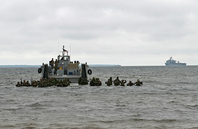 U.S. Marines and Estonian soldiers wade ashore during a combined U.S., Estonian amphibious landing at a beach here. The combined training demonstration was part Baltic Operations 2010, an exercise designed to increase the interoperability of NATO and partner nations in the Baltic Sea region.