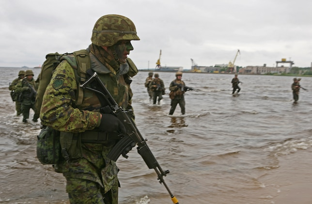 Estonian soldiers and U.S. Marines wade ashore during a combined U.S., Estonian amphibious landing at a beach here. The combined training demonstration was part Baltic Operations 2010, an exercise designed to increase the interoperability of NATO and partner nations in the Baltic Sea region.