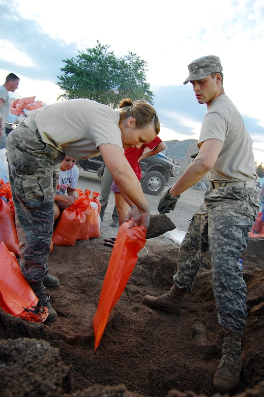 Staff Sgt. Niki Label and Pfc. Taylor Carlson fill sandbags to aid in stopping the rising flood waters of the Popo Agie River, June 11, 2010, in Fremont County, Wyo. Sergeant Label is assigned to the Wyoming Air National Guard's 187th Aeromedical Evacuation Squadron. Private Carlson is assigned to the Wyoming Army National Guard's A Battery, 2-300th Field Artillery. (Photo by Christian Venhuizen)
