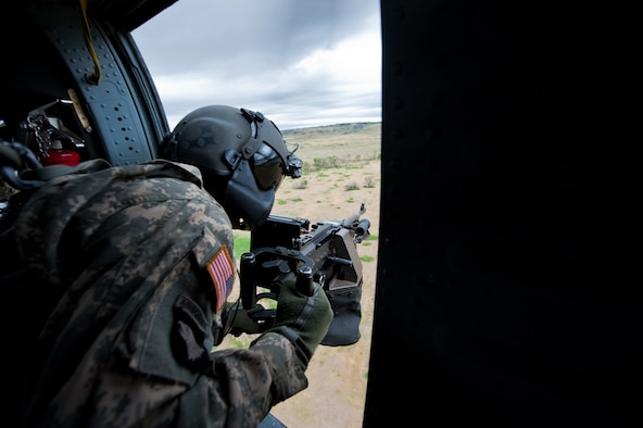 Army Staff Sgt. Marc Belo, UH-60 Black Hawk crew chief of 2nd Battalion, 135th Aviation Regiment, Colorado Army National Guard Army Aviation Support Facility, Buckley Air Force Base, scans the terrain on decent to a landing zone during a live fire demonstration at Fort Carson, Colo. June 12, 2010. (U.S. Air Force photo/Master Sgt. John Nimmo, Sr.) (RELEASED)