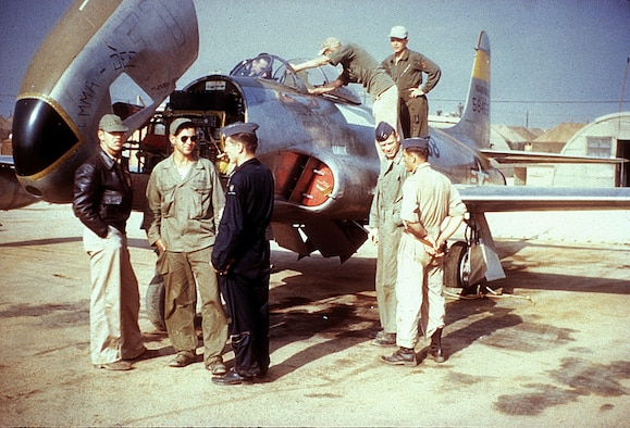"Ground crew prepare to fit the RF-80 ""Emma-Dee"" with nose cameras as reconnaissance pilots  watch. (U.S. Air Force photo)"
