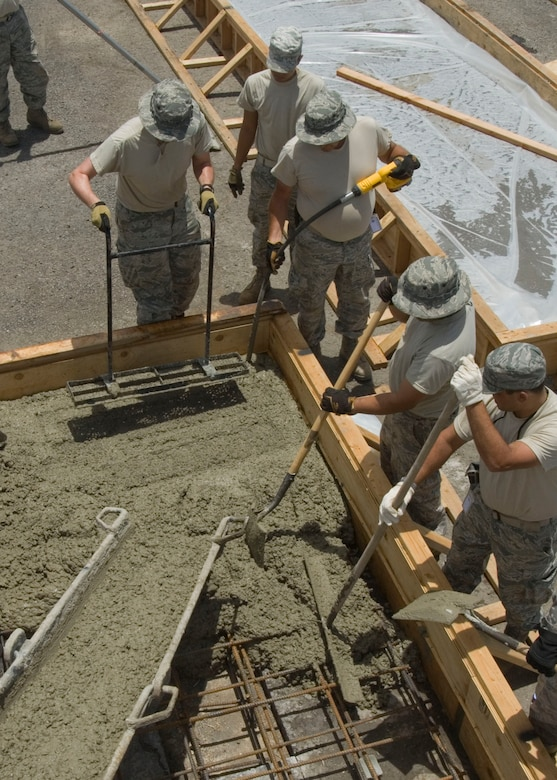 "Airmen from the 146th Civil Engineering Squadron known as the ""dirt boys"" use various tools to evenly distribute concrete during a concrete pour on Pearl City's Naval Base in Hawaii, June 14, 2010. The Civil Engineering Squadron is assisting with various construction projects at Pearl City Naval Base and U.S. Coast Guard Air Station, Barbers Point from June 4-18, 2010. (DoD photo by Airman 1st Class Nicholas Carzis, U.S. Air Force)"