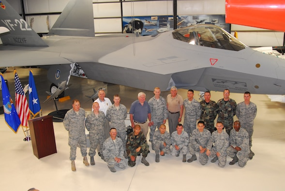 Fourteen of the 22 Airman who were hands-on in the process of bringing the first YF-22 Raptor prototype built, pose in front of the aircraft with Mr. David Ferguson (blue shirt), first Raptor test pilot, Mr. Tom Morgenfeld (tan shirt), last Raptor test pilot and Mr. Fredrick Johnsen (white shirt), Air Force Flight Test Center Museum director, that were instrumental in bringing back to Edwards, its flight-test home.