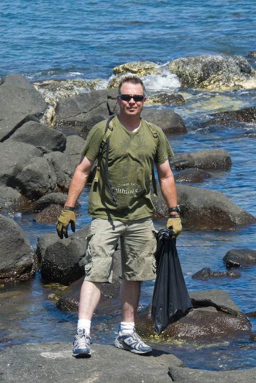 """Master Sgt. Don Simmons helps pick up trash at Laniakea Beach on Oahu's North Shore June 11, 2010. The 146th AW Civil Engineering Squadron participated in the project alongside the organization """"Malama nu Honu,"""" a non-profit group that works to protect the Hawaiian Green Sea Turtle through education, public awareness and conservation. (DoD photo by Airman 1st Class Nicholas Carzis, U.S. Air Force/Released)"""