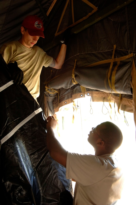 Senior Airmen Phillip Conroy (left) and Markiss Hines, 567th RED HORSE Squadron, install the inner liner to a tent at the temporary encampment that will house more than 250 Airmen, Soldiers, and Marines for New Horizons Panama 2010. (U.S. Air Force photo/Tech. Sgt. Eric Petosky)