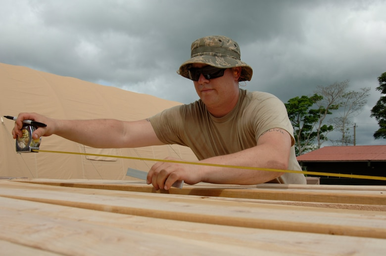 Staff Sgt. Joshua Lasarski, 567th RED HORSE Squadron, measures out plywood for the floor of the dining tent at the temporary encampment that will house more than 250 Airmen, Soldiers, and Marines for New Horizons Panama 2010. (U.S. Air Force photo/Tech. Sgt. Eric Petosky)